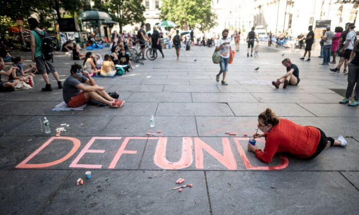 """People sit on the ground at a protest to defund the police in an area demonstrators named """"City Hall Autonomous Zone"""" near City Hall in Lower Manhattan in New York City, N.Y., on June 26, 2020. (Johannes Eisele/AFP via Getty Images)"""