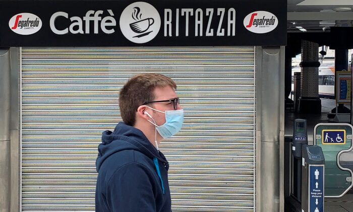 A pedestrian wearing a mask walks past a closed-down and shuttered Caffe Ritazza coffee and food outlet in a train station in London on July 1, 2020. (Daniel Leal-Olivas/AFP via Getty Images)