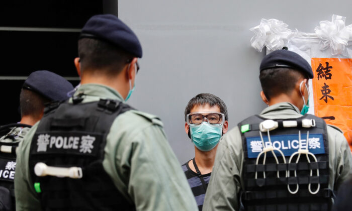 Police search a pro-democracy protester during a demonstration on July 1, 2020. (Tyrone Siu/Reuters)