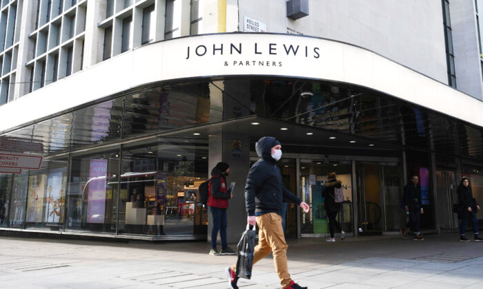 A man wearing a protective face mask walks past the front entrance of John Lewis department store on Oxford Street in central London on the afternoon of March 21, 2020. (Daniel Leal-Olivas/AFP via Getty Images)