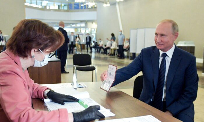 Russian President Vladimir Putin shows his passport to a member of an election commission as he arrives to take part in voting at a polling station in Moscow, Russia, on July 1, 2020. (Alexei Druzhinin, Sputnik, Kremlin Pool Photo via AP)