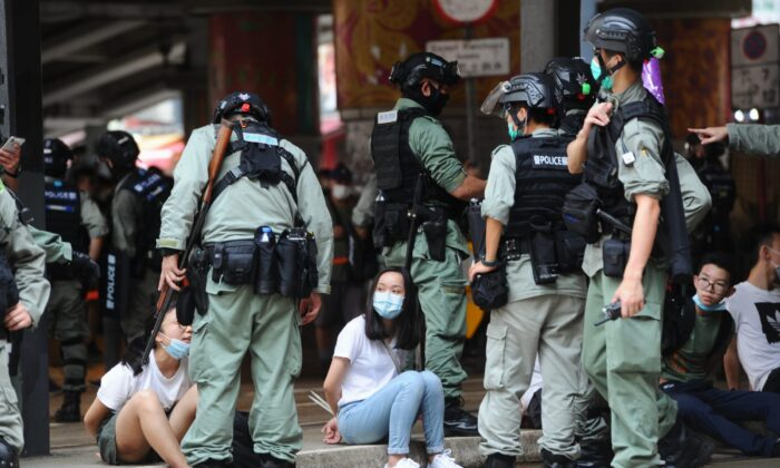 Two protesters are arrested by the police in Causeway Bay, Hong Kong, on July 1, 2020. (Song Bilung/The Epoch Times)