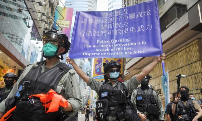 Police display a public announcement banner showing a warning to protesters in Causeway Bay before the annual handover march in Hong Kong on July 1, 2020. (Vincent Yu/AP)
