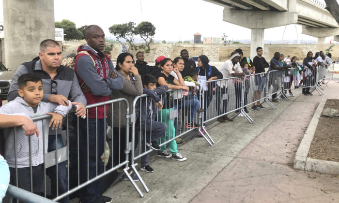 Asylum seekers listen to names being called from a waiting list to claim asylum at a border crossing in Tijuana, Mexico, on Sept. 26, 2019. (Elliot Spagat/AP Photo)