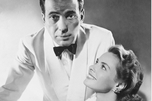 """man in white dinner jacket and bowtie and seated woman in """"Casablanca"""""""