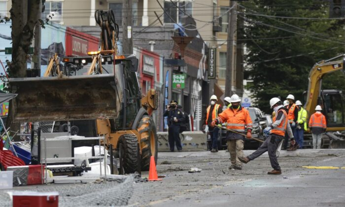 Workers remove items left behind after police cleared the Capitol Hill Occupied Protest (CHOP) and retook the department's East Precinct in Seattle, Washington, on July 1, 2020. (Jason Redmond/AFP via Getty Images)