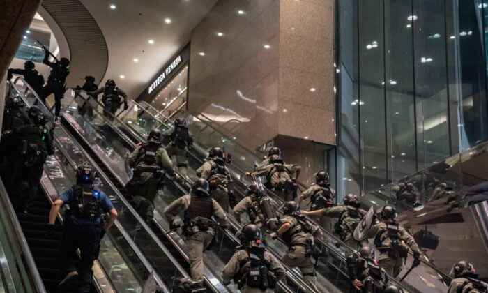Riot police officers charge up escalators and shoot pepperball projectiles at a shopping mall during an anti-national security law demonstration  in Hong Kong, China, on July 1, 2020. (Anthony Kwan/Getty Images)