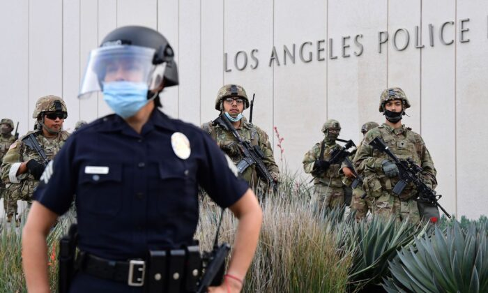 A police officer stands with armed members of the National Guard facing protesters in front of the Los Angeles Police Department in Los Angeles, California, on June 1, 2020. (Frederic J. Brown/AFP via Getty Images)