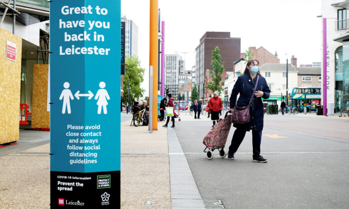 A woman wearing a protective face mask walks in Leicester, UK, on June 30, 2020. (Molly Darlington/Reuters)