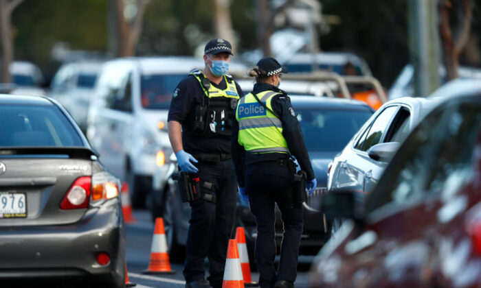 Police check the identification of members of the public at a pop up road block in Broadmeadows, Victoria to ensure they have legitimate reasons for leaving one of the 10 postcode hotspots on 2 July, 2020 in Melbourne, Australia. (Darrian Traynor/Getty Images)