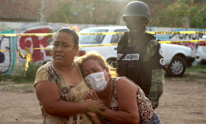 Women react outside a drug rehabilitation facility where assailants killed at least 24 people, according to Guanajuato state police, in Irapuato, Mexico, on July 1, 2020. (Karla Ramos/Reuters)
