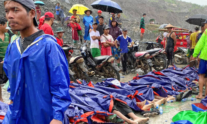 People walk and gather near dead bodies of jade scavengers who were killed in a landslide covered with plastic and lined up near a jade mining area in Hpakant, Kachine state in northern Burma, on July 2, 2020. (Zaw Moe Htet/AP Photo)