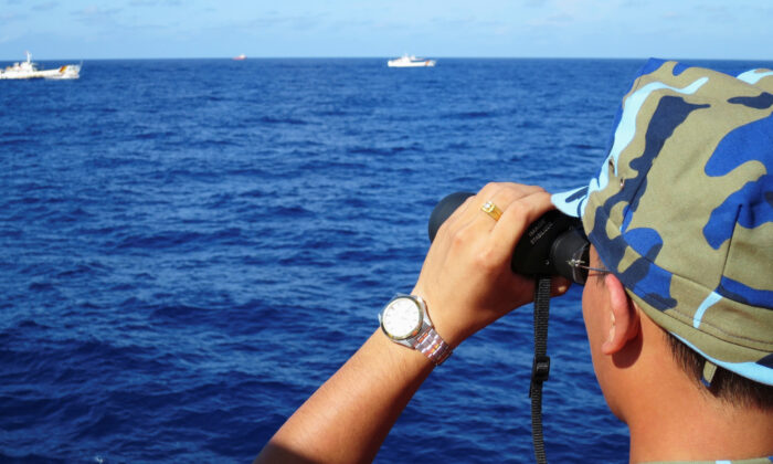 A crewman from a Vietnamese coastguard ship looks out at sea as Chinese coastguard vessels give chase to Vietnamese ships in the South China Sea, on July 15, 2014. (Martin Petty/Reuters)