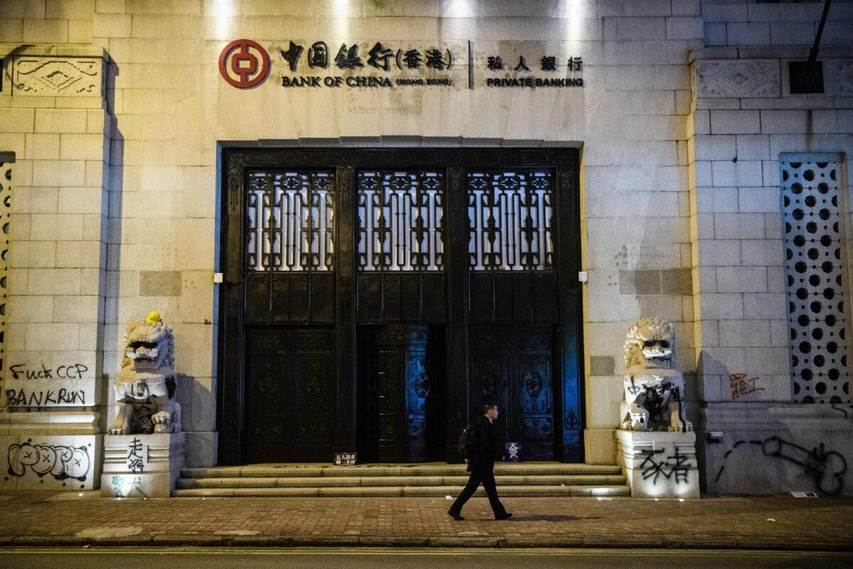 Muž prochází kolem graffiti zanechaných protestujícími na staré budově Bank of China po pro-demokratickém shromáždění ve Victoria Park v Hongkongu 8. prosince 2019. (Anthony Wallace / AFP prostřednictvím Getty Images)