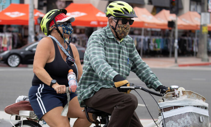 A couple ride a tandem bike at Huntington Beach, Calif., on July 1, 2020. (Reuters/Mike Blake)