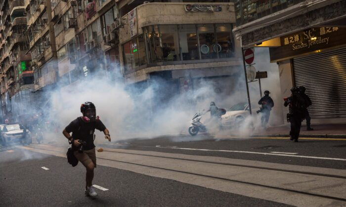 Riot police deploy tear gas as they clear protesters from a road during a rally against a new national security law in Hong Kong on July 1, 2020, on the 23rd anniversary of the city's handover from Britain to China. (Dale de la Rey/AFP via Getty Images)