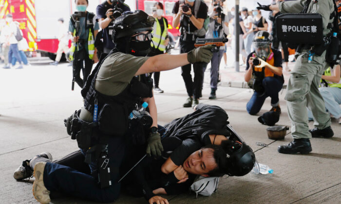 A police officer raises his pepper spray handgun as he detains a man during a march against the national security law at the anniversary of Hong Kong's handover to China from Britain in Hong Kong, on July 1, 2020. (Tyrone Siu/Reuters)