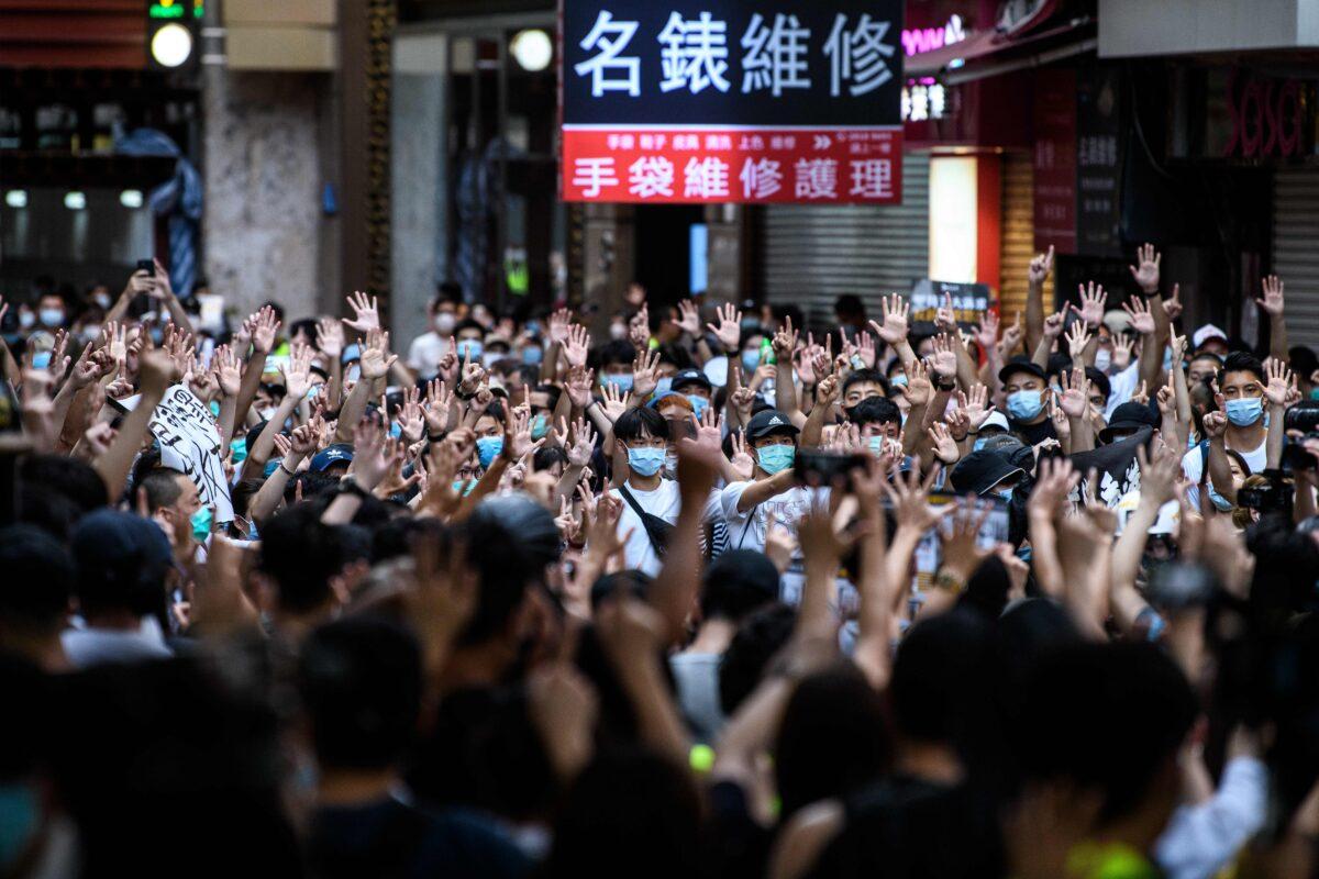 Protestující skandují slogany a gesta během shromáždění proti novému zákonu o národní bezpečnosti v Hongkongu 1. července 2020, k 23. výročí předání města z Británie do Číny. (Anthony Wallace / AFP prostřednictvím Getty Images)