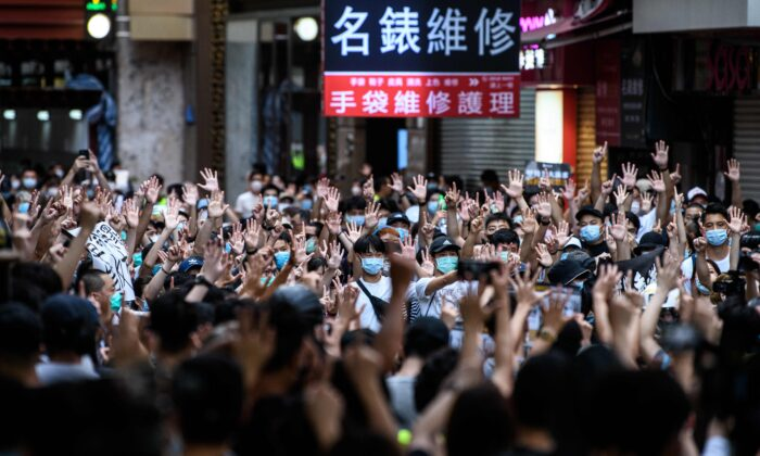 Protesters chant slogans and gesture during a rally against the new national security law in Hong Kong on July 1, 2020, on the 23rd anniversary of the city's handover from Britain to China. (Anthony Wallace/AFP via Getty Images)