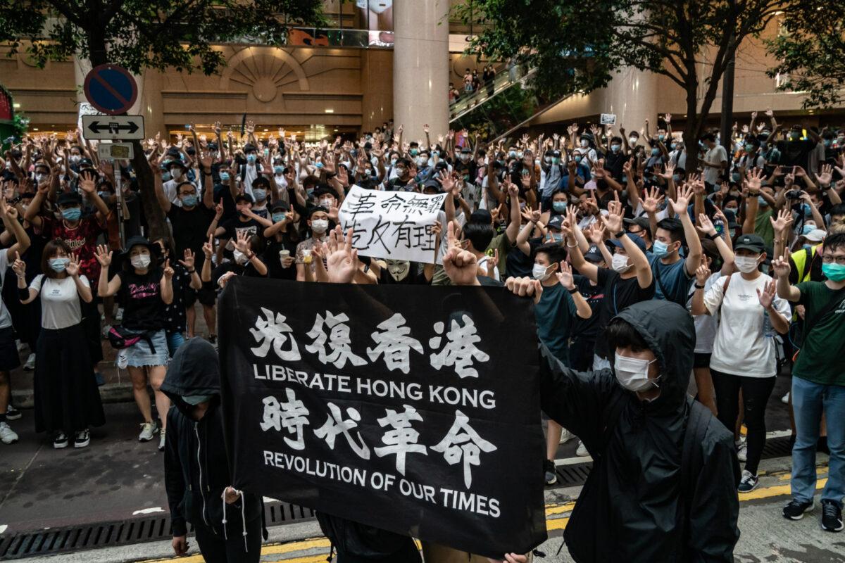 """Pořádková policie začala zatýkat protestující, kteří drží vlajku s nápisy """"Osvoboďte Hongkong – revoluce naší doby."""" Hongkong, 1. července 2020. (Anthony Kwan / Getty Images)"""