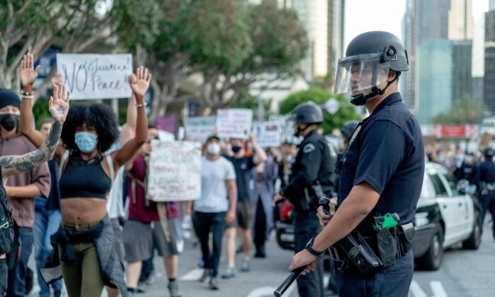 Protesters march past LAPD officers during a demonstration over the death of George Floyd, in Los Angeles on June 6, 2020. (Kyle Grillot/AFP via Getty Images)