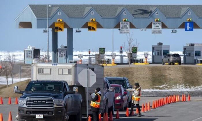 Provincial health department workers stop traffic that has crossed the Confederation Bridge in Borden-Carleton, P.E.I. on March 22, 2020. (The Canadian Press/Andrew Vaughan)
