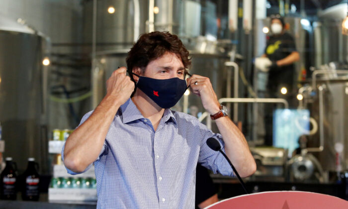 Canada's Prime Minister Justin Trudeau removes his face mask as he visits the Big Rig Brewery, which utilizes the Canada Emergency Wage Subsidy given to businesses affected by the coronavirus disease (COVID-19) outbreak, in Kanata, Ontario on June 26, 2020.  (Reuters/Patrick Doyle)