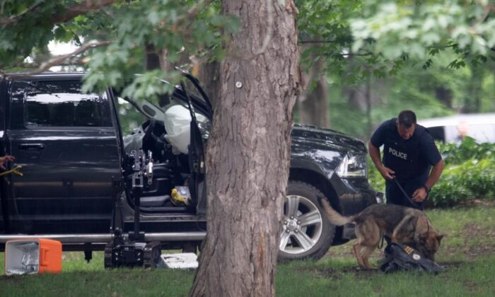 An RCMP officer works with a police dog as they move through the contents of a pick-up truck on the grounds of Rideau Hall in Ottawa, on July 2, 2020. (The Canadian Press/Adrian Wyld)