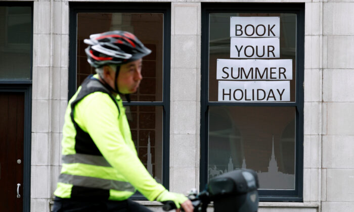 A man rides a bicycle past a travel agents store, amid the coronavirus disease (COVID-19) outbreak, in Manchester, England, on July 2, 2020. (Phil Noble/Reuters)