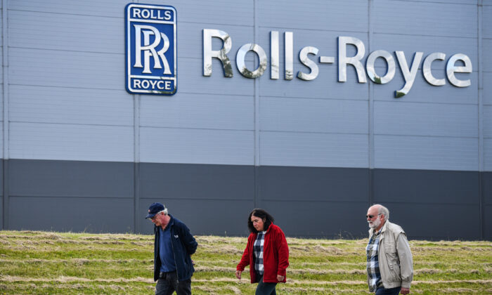 People walk past the Rolls Royce Inchinan factory on June 11, 2020, in Inchinnan, Scotland. Jet engine manufacturer Rolls-Royce is expected to cut 20 percent of its workforce, including 700 jobs at the Inchinnan plant, following a sharp decline in business as a result of the coronavirus outbreak. (Jeff J Mitchell/Getty Images)