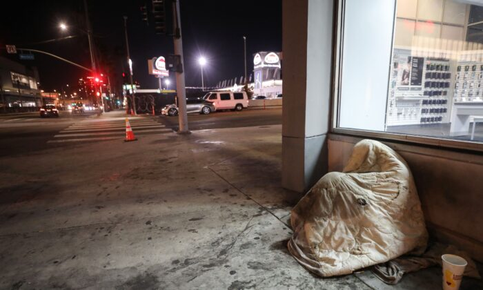 A homeless person rests beneath a blanket on Sunset Boulevard amid the COVID-19 pandemic in Los Angeles on July 1, 2020. (Mario Tama/Getty Images)