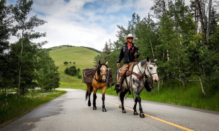 Filipe Masetti Leite, a Brazilian cowboy who has been riding from Alaska to Calgary and who has also been chosen as the parade marshal for the Calgary Stampede, rides his pony Smokey as pack pony Mack follows along near Waiparous Village, Alta., onJune 29, 2020. (The Canadian Press/Jeff McIntosh)