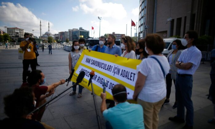 Protesters from Amnesty International talk to the media as they stage a protest outside a court in Istanbul, on July 3, 2020, where the trial of 11 prominent human rights activists for terror-related charges and adjourned proceedings continued. (Emrah Gurel/AP Photo)