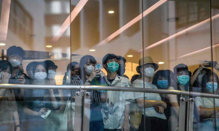 Bystanders watch protesters on a street below a shop during a rally against a new national security law in Hong Kong on July 1, 2020. (Anthony Wallace/AFP via Getty Images)