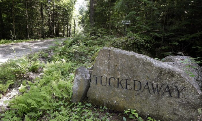 """A boulder inscribed with """"Tucked Away"""" sits beside a road going to an estate where Ghislaine Maxwell was taken into custody, in Bradford, N.H., on July 2, 2020. (Steven Senne/AP Photo)"""