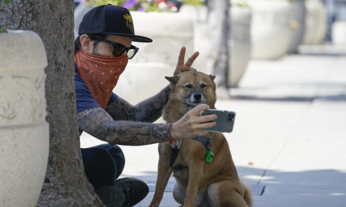 Andrew Stuart wears a bandana as a mask while taking a selfie with his dog, Voltron, on Sunset Blvd, in West Hollywood, Calif., on July 2, 2020. (Ashley Landis/AP Photo)