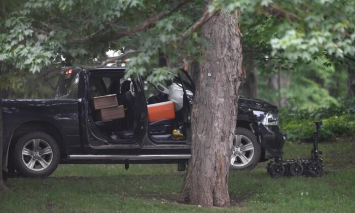 A police robot is shown near a pickup truck inside the grounds of Rideau Hall in Ottawa on July 2, 2020. (The Canadian Press/Adrian Wyld)