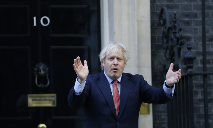 Britain's Prime Minister Boris Johnson applauds on the doorstep of 10 Downing Street in London on May 28, 2020. (Kirsty Wigglesworth/AP Photo)