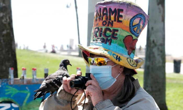 Vendor Vivianne Robinson, wearing a mask to protect from the coronavirus, takes a photo with a pigeon perched on her hand along the Venice Beach strand, on July 3, 2020, in Los Angeles. (Richard Vogel/AP Photo)