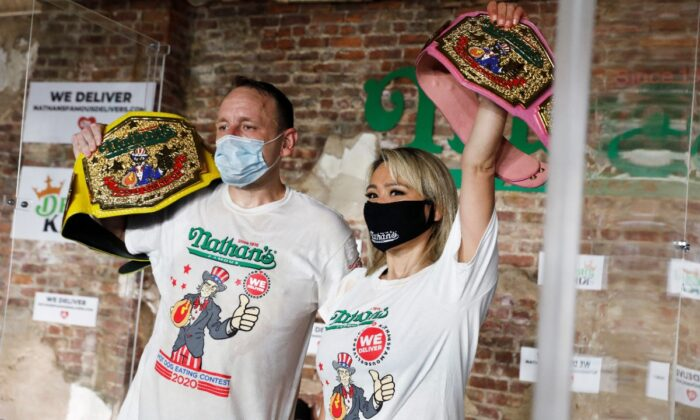 Men's champion Joey Chestnut and women's champion Miki Sudo pose together after winning the Nathan's Famous Fourth of July International Hot Dog Eating Contest in Brooklyn, in New York City, July 4, 2020. (Andrew Kelly/Reuters)