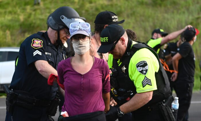 Police arrest a protester who helped block the road to Mount Rushmore National Monument in Keystone, S.D., on July 3, 2020. (Andrew Caballero-Reynolds/AFP via Getty Images)