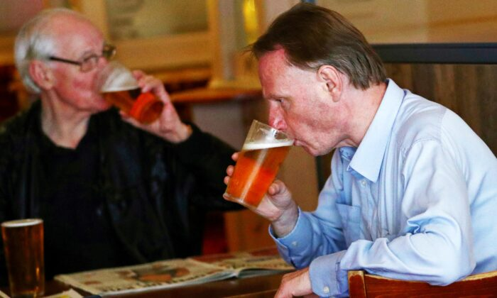 Customers drink beer at The Holland Tringham Wetherspoons pub after it reopened following the outbreak of COVID-19, in London, on July 4, 2020. (Hannah McKay/Reuters)