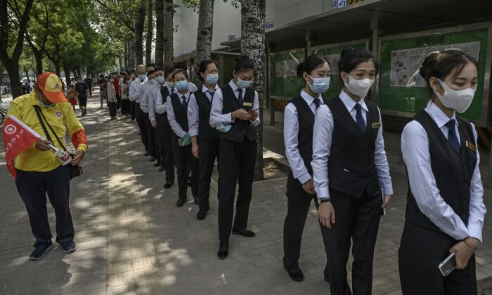 Chinese service industry workers wait in line for nucleic acid swab tests for COVID-19 at a testing site in Beijing on July 1, 2020. (Kevin Frayer/Getty Images)