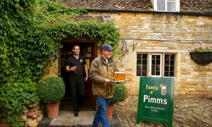 A member of bar staff helps a customer to carry drinks out to the garden as the Plough Inn in Ford, central England reopens on July 4, 2020, as restrictions are further eased during the novel coronavirus COVID-19 pandemic. (Geoff Caddick/AFP via Getty Images)
