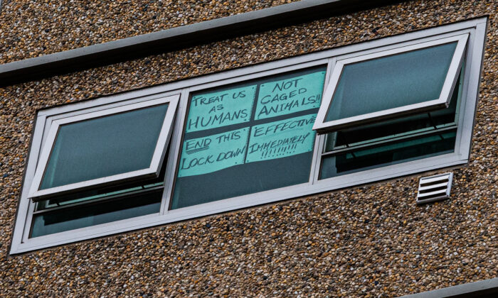 A sign is seen stuck to a window reading 'Treat us as humans not caged animals end this lockdown effective immediately' at the Flemington Public housing flats in Melbourne, Australia on July 05, 2020. (Asanka Ratnayake/Getty Images)