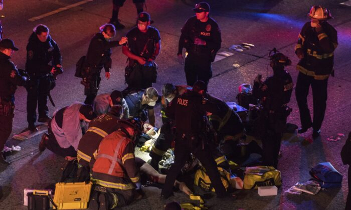 Emergency workers tend to an injured person on the ground after a driver struck two protesters on I-5 in Seattle, Wash., on July 4, 2020. (James Anderson via AP)