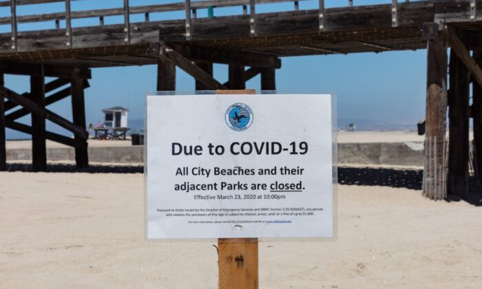 A beach closure sign sits in the sand at the Seal Beach Pier in Seal Beach, Calif., on July 4, 2020. (John Fredricks/The Epoch Times)