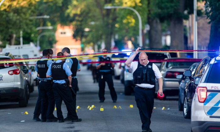 Chicago police officers investigate the scene of a deadly shooting in Chicago, Ill., on July 5, 2020. (Tyler LaRiviere/Chicago Sun-Times via AP)