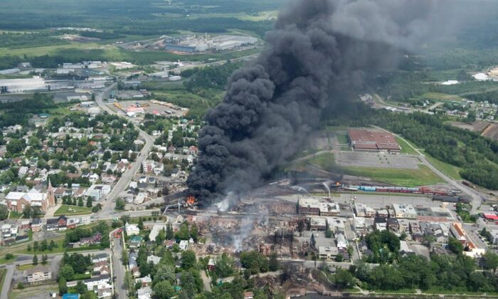 Smoke rises from railway cars that were carrying crude oil after derailing in downtown Lac-Mégantic, Que., on July 6, 2013. (The Canadian Press/Paul Chiasson)