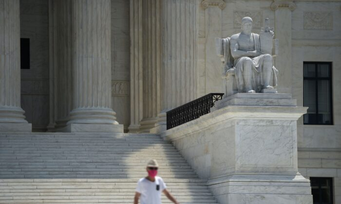 A man in a facemask walks down the steps of the U.S. Supreme Court in Washington on July 6, 2020. (Brendan Smialowski/AFP via Getty Images)